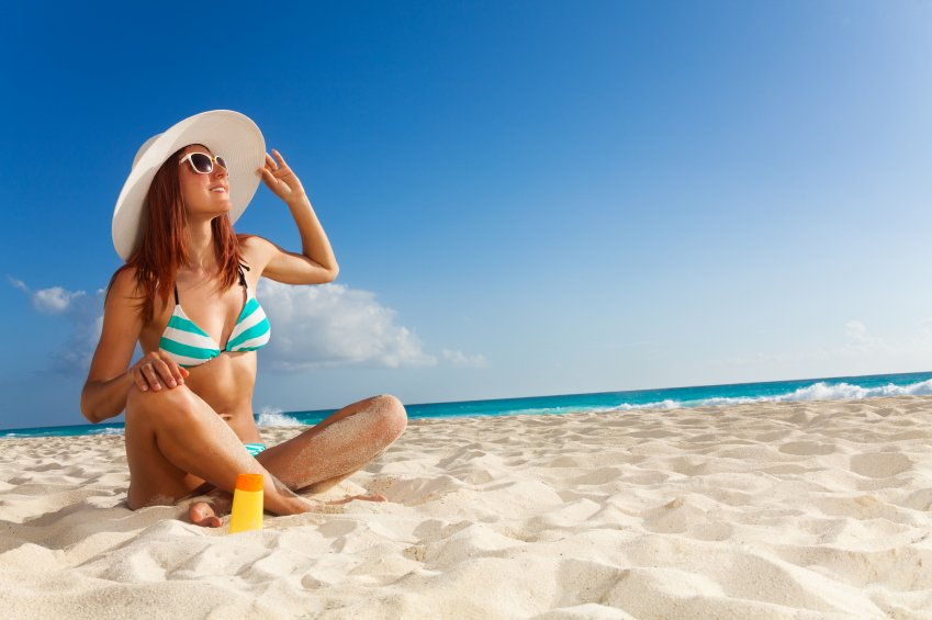 Tanned girl in blue striped bikini and big white hat relaxing on sunny beach
